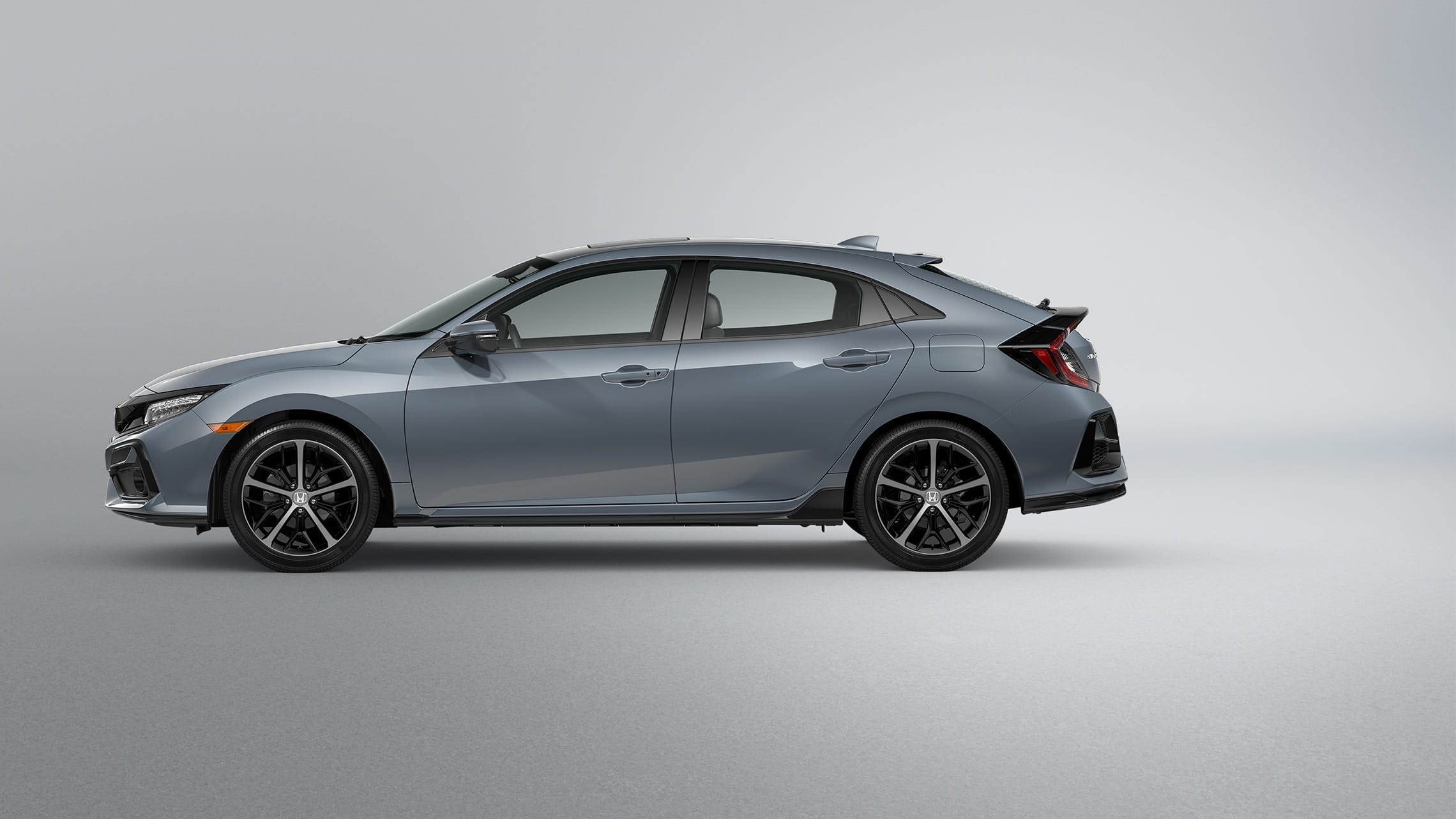 Driver-side profile view of 2020 Honda Civic Sport Touring Hatchback in Sonic Gray Pearl.